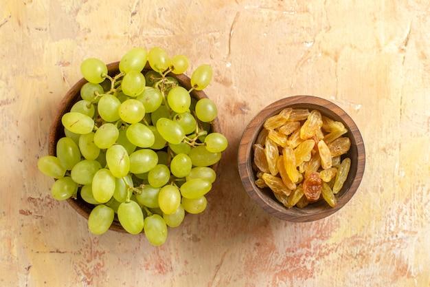 Vista superior em close-up de taças de uvas verdes e passas na mesa