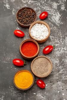 Vista superior em close-up de temperos - cinco tigelas de temperos coloridos e tomates na mesa escura