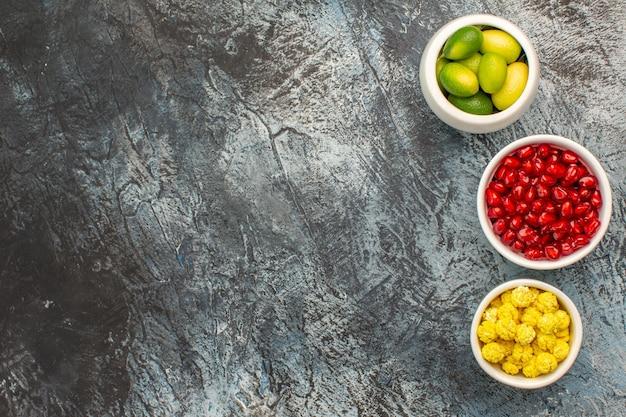 Vista superior em close-up de tigelas de doces com sementes de frutas cítricas de romã e doces amarelos