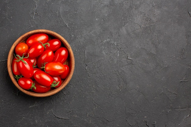 Vista superior em close-up de tomates em uma tigela tomates vermelhos maduros em uma tigela no lado esquerdo da mesa escura