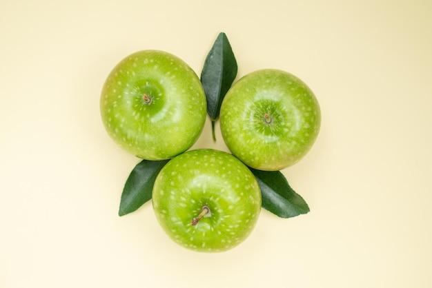 Vista superior em close-up de três maçãs apetitosas com folhas na superfície branca