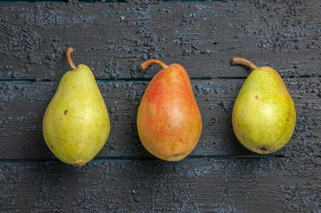 Vista superior em close-up de três peras na mesa, duas peras verdes e uma pera vermelho-amarela no centro da mesa cinza