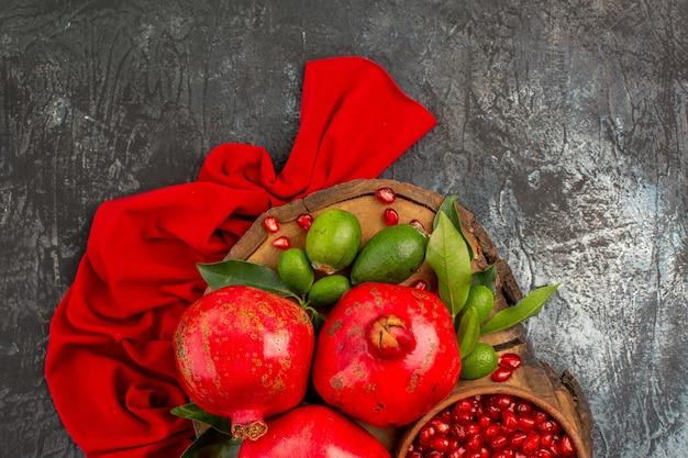Vista superior em close-up de três romãs e sementes de romã na toalha de mesa vermelha