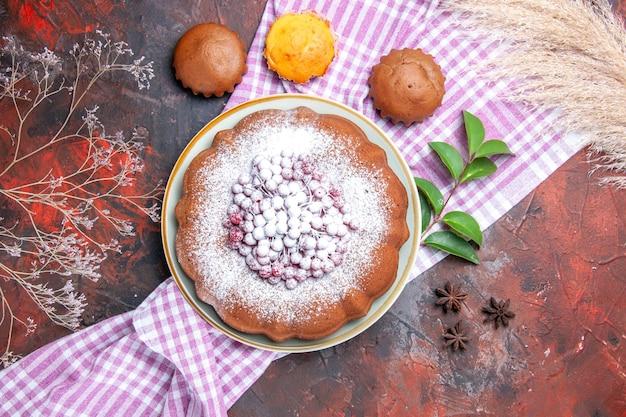 Vista superior em close-up de um bolo três bolinhos de folhas de bolo na toalha de mesa xadrez de anis estrelado
