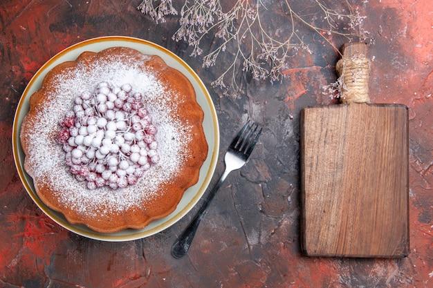 Vista superior em close-up de um bolo - uma tábua de madeira com garfo ao lado do apetitoso bolo com groselha