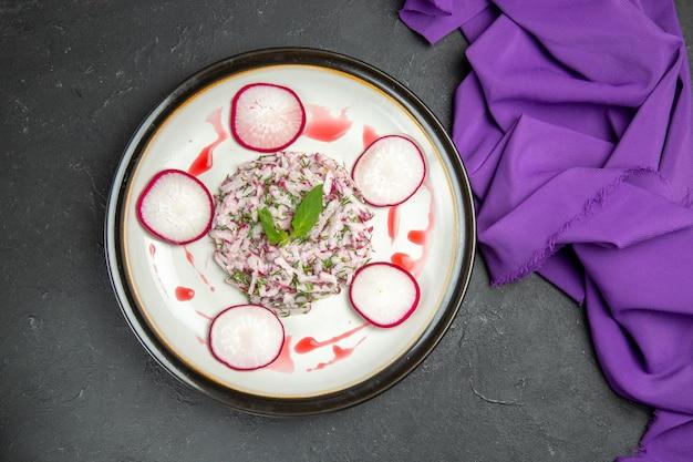 Vista superior em close-up de um prato apetitoso de ervas de rabanete e toalha de mesa roxa com molho