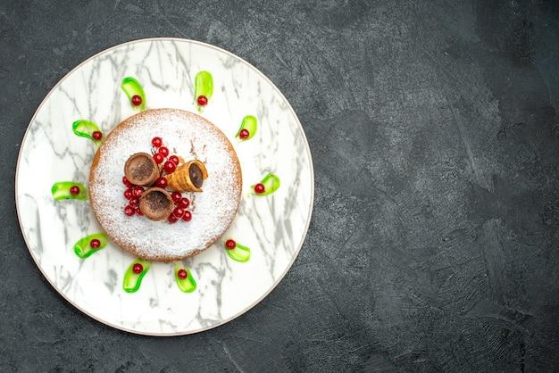 Vista superior em close-up de um prato de bolo cinza com waffles de açúcar de confeiteiro de frutas