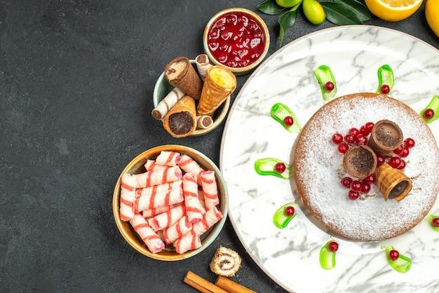 Vista superior em close-up de um prato de bolo com geleia de bolo waffles frutas cítricas biscoitos canela em pau doces