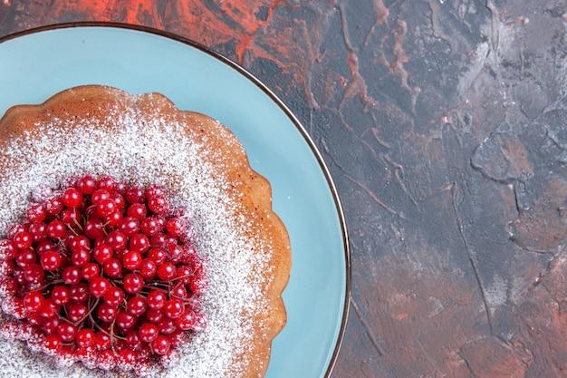 Vista superior em close-up de um prato prato azul de um apetitoso bolo com frutas vermelhas na mesa