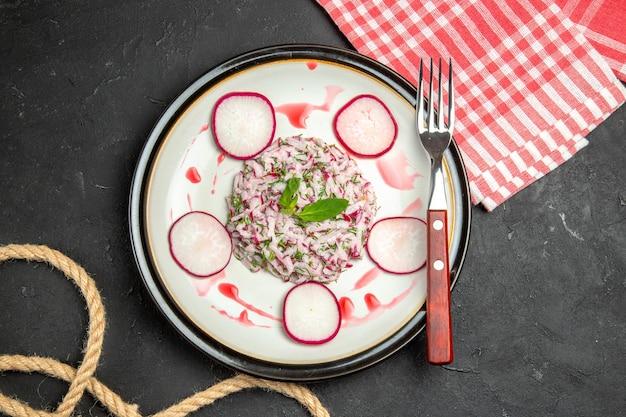 Vista superior em close-up de um prato, um prato de corda de garfo avermelhado e a toalha de mesa quadriculada