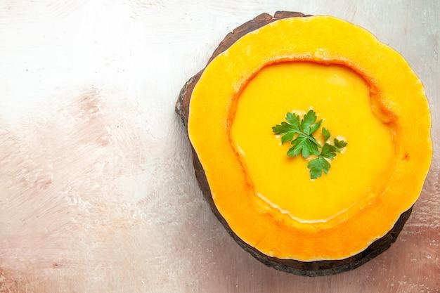 Vista superior em close-up de uma tábua de sopa de madeira com uma sopa apetitosa com ervas na abóbora