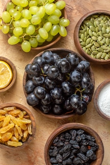 Vista superior em close-up de uvas, cachos de uvas, passas, açúcar, limão, sementes de abóbora em tigelas
