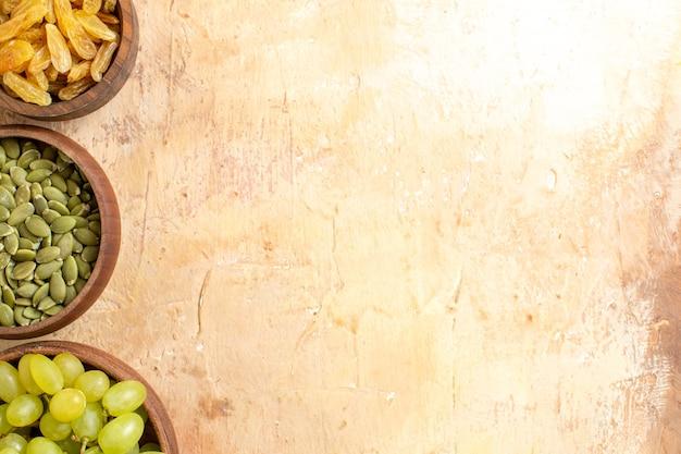 Vista superior em close-up de uvas uvas verdes passas sementes de abóbora em tigelas marrons