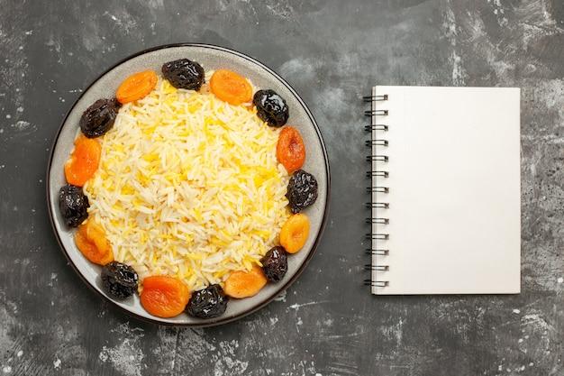 Vista superior em close-up do arroz com arroz e frutas secas no bloco de notas