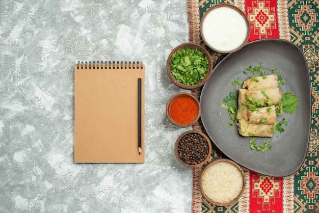 Vista superior em close-up do prato com prato de ervas com repolho recheado e tigelas de ervas com especiarias de papel preto