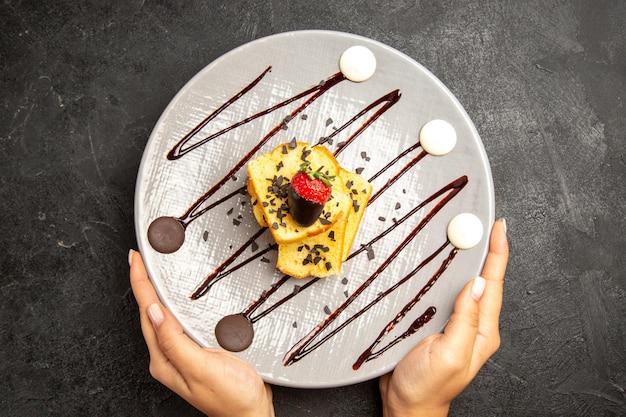 Vista superior em close-up do prato de bolo de doces com morangos cobertos de chocolate e calda de chocolate nas mãos