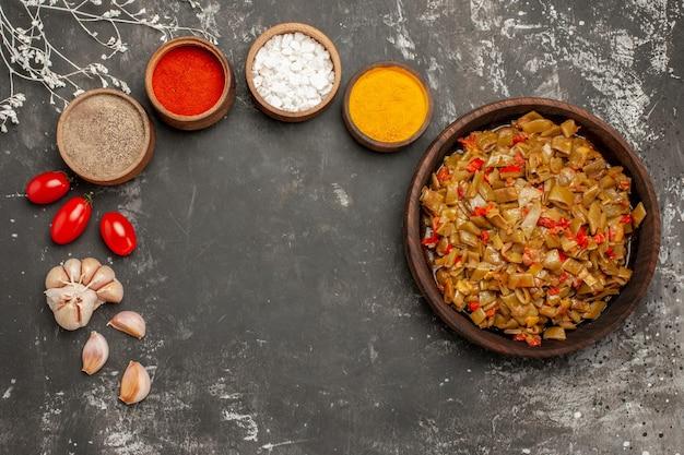 Vista superior em close-up do prato de tomate feijão verde ao lado de tigelas de especiarias coloridas e alho na mesa escura