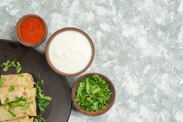 Vista superior em close-up do prato na mesa repolho recheado no prato ao lado da tigela com ervas, especiarias e creme de leite azedo no lado esquerdo da mesa cinza