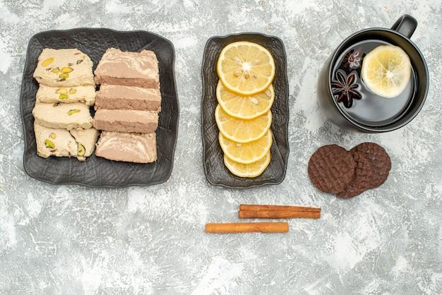 Vista superior em close-up doces, limão, semente de girassol, halva no prato, canela, uma xícara de chá