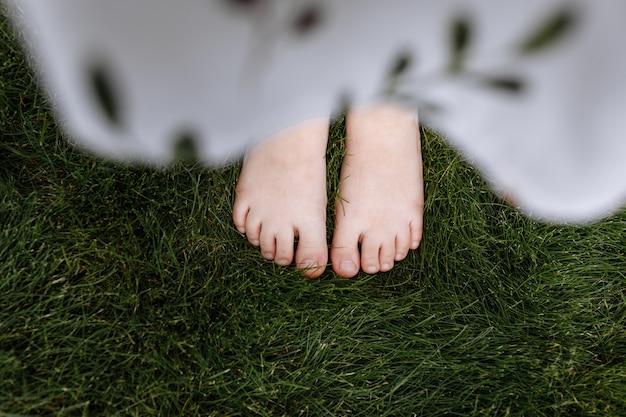 Vista superior em close-up dos pés descalços de uma criança na grama verde