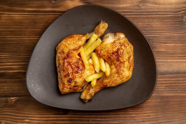 Vista superior em close-up em um prato de fast food marrom com apetitosas batatas fritas e coxas de frango na mesa de madeira