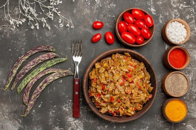 Vista superior em close-up feijão verde e prato de especiarias de feijão verde ao lado dos quatro tipos de especiarias garfo tomate na tigela e feijão verde na mesa