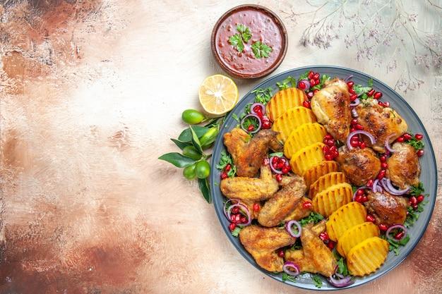 Vista superior em close-up frango ao molho de limão frango com batatas sementes de ervas de romã