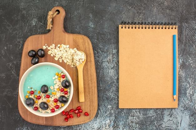 Vista superior em close-up, frutas, aveia, uvas, sementes, colher de romã, lápis, quadro, caderno