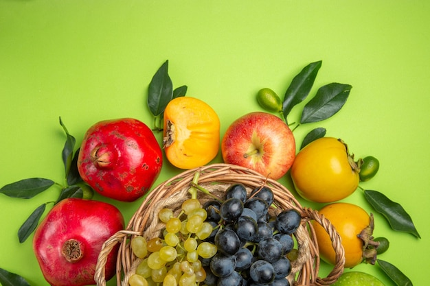 Vista superior em close-up frutas caquis maçãs cesta de cachos de folhas de uvas