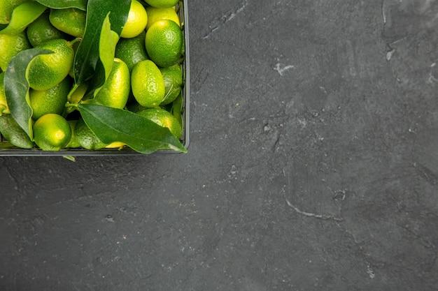 Vista superior em close-up frutas cítricas com folhas na cesta sobre a mesa
