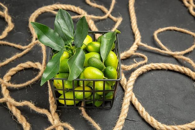 Vista superior em close-up frutas cítricas frutas cítricas na cesta ao lado da corda