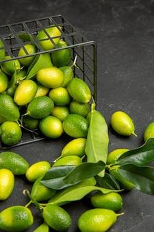 Vista superior em close-up frutas cítricas frutas cítricas na cesta na mesa escura