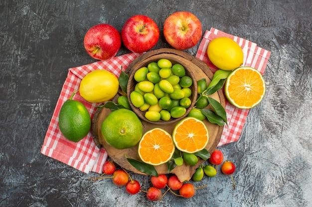 Vista superior em close-up frutas cítricas frutas cítricas no quadro cerejas maçãs na toalha de mesa