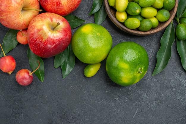Vista superior em close-up frutas cítricas maçãs cerejas tangerinas tigela de frutas cítricas com folhas