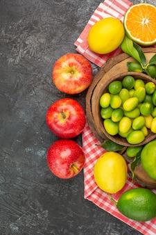Vista superior em close-up frutas cítricas maçãs frutas cítricas no quadro sobre a toalha de mesa quadriculada