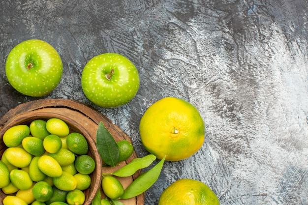 Vista superior em close-up frutas cítricas maçãs tangerinas em volta da tábua de cortar