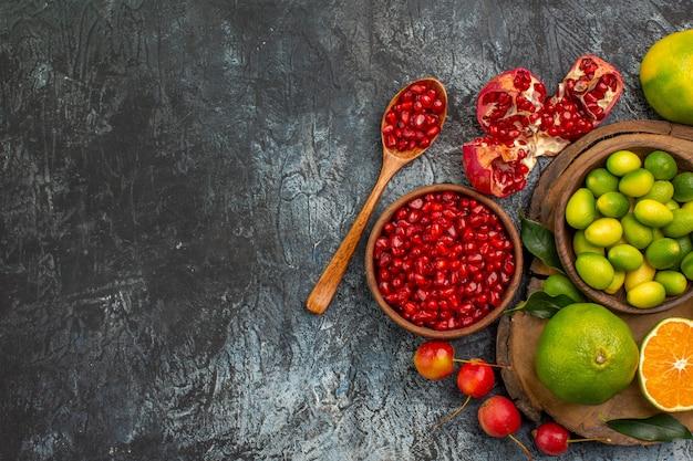 Vista superior em close-up frutas cítricas sementes de romã frutas cítricas na tábua de corte Foto gratuita