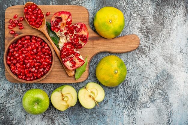 Vista superior em close-up, frutas cítricas, tangerinas, maçãs em torno de sementes de romã no quadro