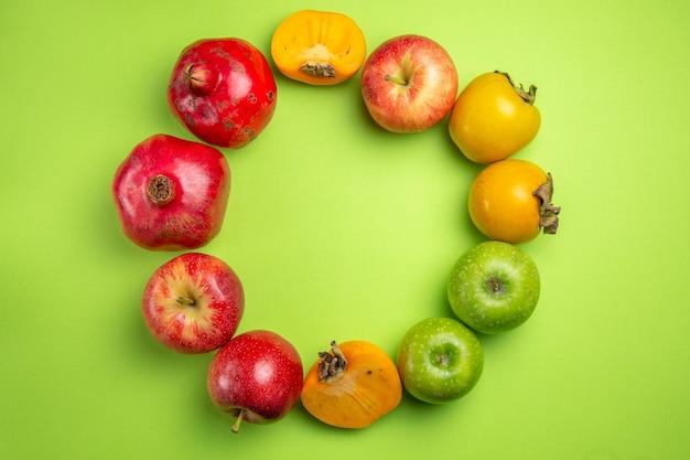 Vista superior em close-up frutas coloridas caquis maçãs romã na mesa verde