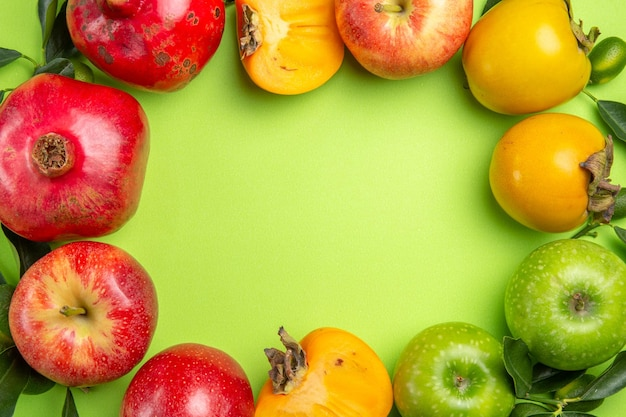 Vista superior em close-up frutas coloridas maçãs coloridas caquis romã com folhas na mesa