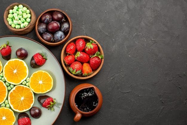 Vista superior em close-up frutas doces verdes, morango coberto com chocolate e laranja picada e tigelas de frutas vermelhas e calda de chocolate na mesa