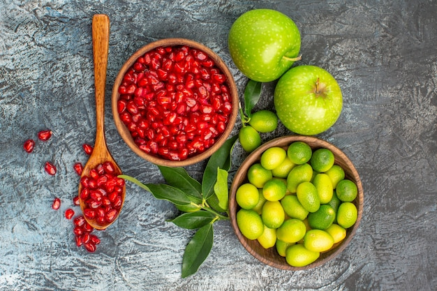 Vista superior em close-up frutas maçãs sementes de romã colher frutas cítricas na tigela