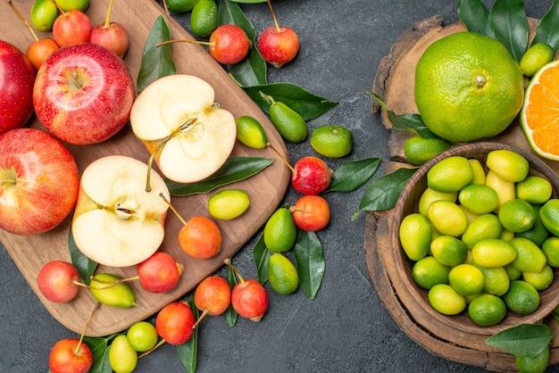 Vista superior em close-up frutas maçãs vermelhas no quadro cerejas e frutas cítricas na tigela