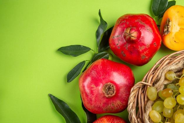 Vista superior em close-up frutas romãs caqui cachos de uvas e folhas