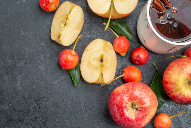 Vista superior em close-up frutas uma xícara de chá, maçãs, cerejas com folhas
