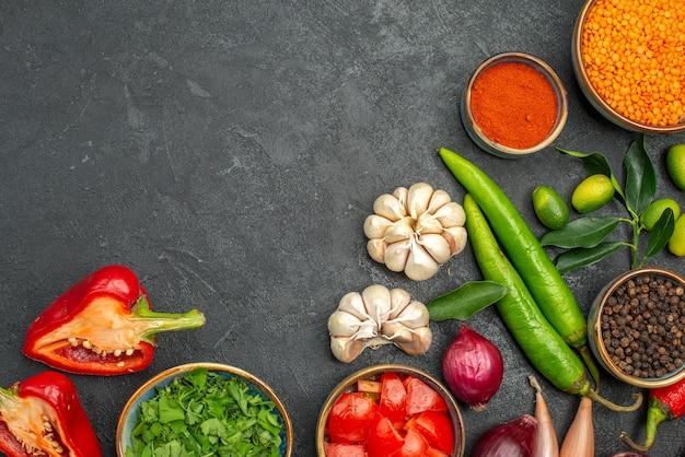 Vista superior em close-up legumes lentilha ervas especiarias cebola alho pimenta pimenta tomates pimentões