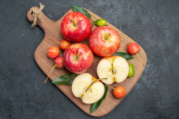 Vista superior em close-up maçãs maçãs cerejas com folhas na tábua