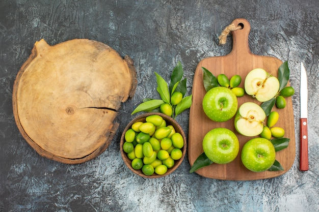 Vista superior em close-up maçãs maçãs com folhas tigela de faca de frutas cítricas a tábua