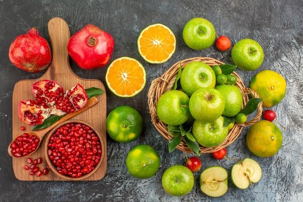 Vista superior em close-up maçãs maçãs na cesta frutas cítricas cerejas tabuleiro de romã