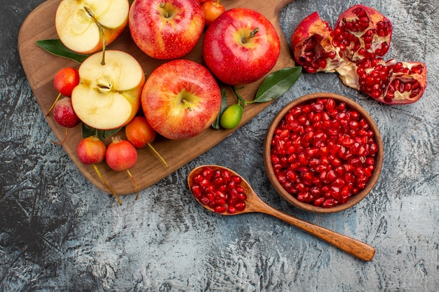 Vista superior em close-up maçãs romã colher na tábua com cerejas maçãs